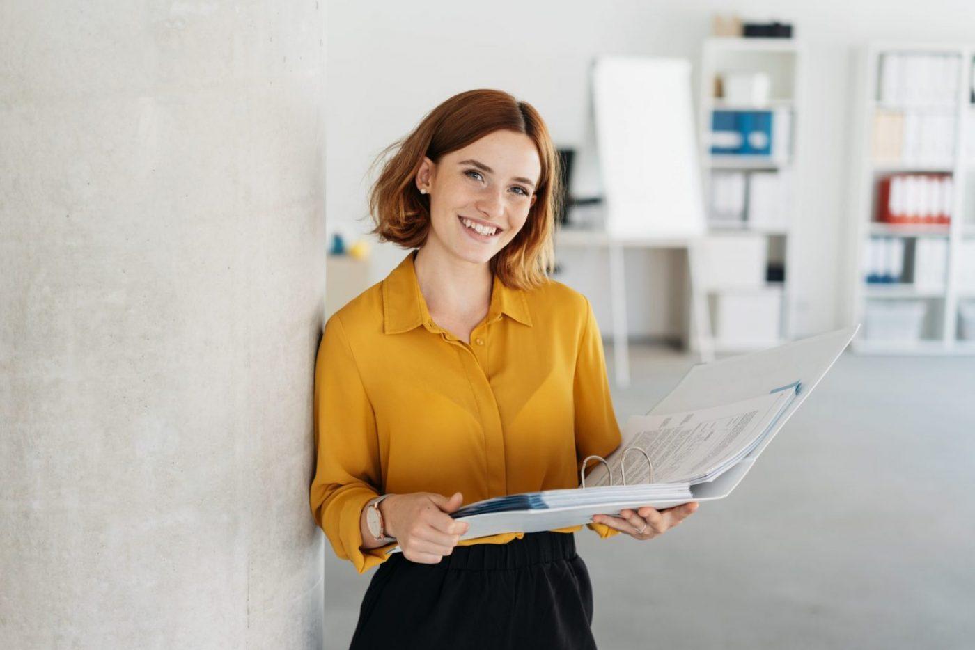 jeune femme rousse, souriante, tenant un classeur